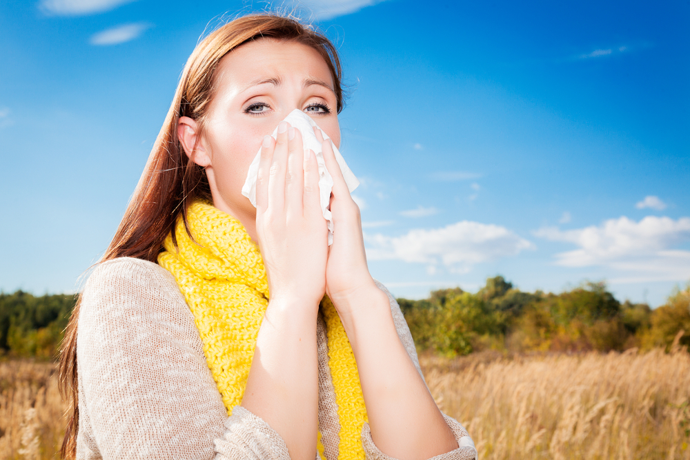 person with allergies sneezing in a field